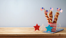 Happy Independence Day, 4th Of July Celebration Concept With Twisted Hot Dog Sausages And USA Flag On Wooden Table
