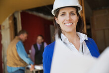 Portrait Of Female Architect With Blueprint At Construction Site