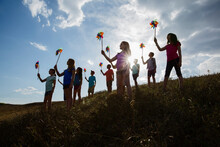 Low Angle View Of Schoolchildren Holding Pinwheels During Field Trip