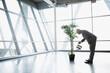 Leinwandbild Motiv Businessman watering potted tree in modern office