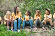 Camp Counselor And Children Sitting On Log In Forest