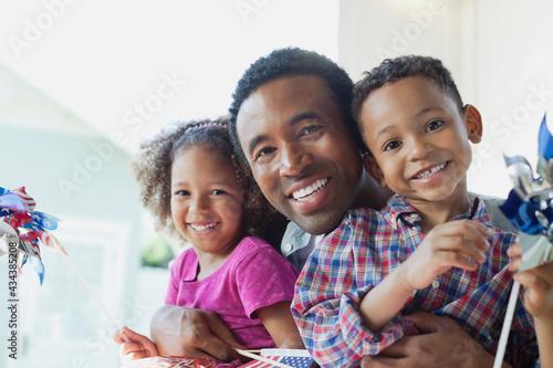 Obraz na plátne Portrait of happy father with children holding pinwheels