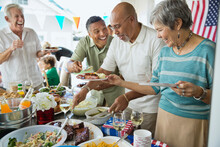 Cheerful Friends And Family At Buffet Table On Fourth Of July