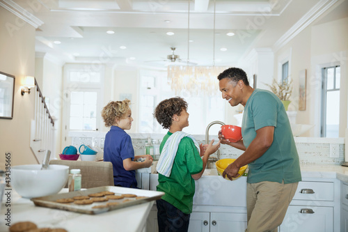 Happy children helping father in domestic kitchen