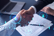 Recruitment Concept To Hiring Of A New Talented Specialists For International Company. Handshake To Sign In Of Employment Agreement. Social Media Hologram Icons Over The Table With Documents.