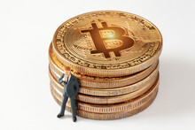 Tiny Thinking Businessman Figurine While Leaning To Shiny Bitcoin Stack On White Background. Developing A Business Strategy. Cryptocurrency, Blockchain Or Trading Concept.