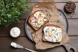 Fototapeta Kawa jest smaczna - Delicious sandwiches with radish, egg, cream cheese and microgreens on wooden table, flat lay