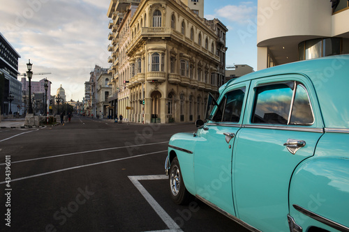 Fotografiet Old car on streets of Havana with colourful buildings in background