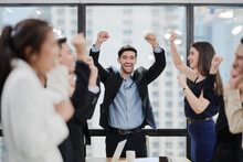 In A Meeting Room, A Manager And His Team Are Very Happy With Their Team Performance.