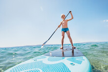 Wide-angle View Shot Of Laughing Blonde Teenager Boy Rowing Stand-up Paddleboard. Active Family Summer Vacation Time Near The Sea Concept Image.