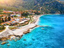 Aerial View Of Beautiful Hotel And Blue Sea At Sunny Day In Summer In Oludeniz, Turkey. Top View Of Buildings, Clear Water, Stones, Beach, Green Palm Trees, Mountain. Luxury Resort. Tropical Landscape
