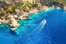 Speed Boat In Blue Sea At Sunrise In Summer. Aerial View Of Floating Motorboat In Sea Bay. Tropical Landscape With Yacht, Clear Water, Rocks , Stones, Mountain, Green Trees. Top View. Oludeniz, Turkey