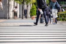 新聞を持って横断歩道を渡るビジネスマンの後ろ姿