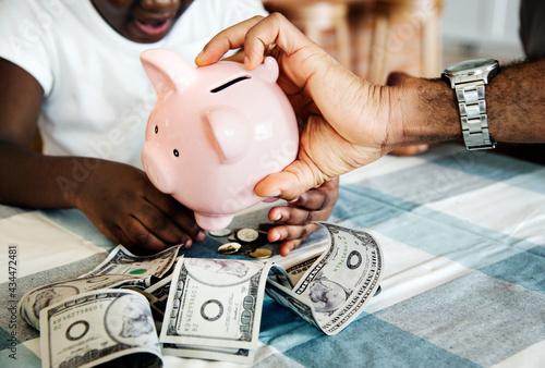 Dad and daughter saving money to piggy bank Fotobehang