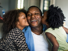 African Children Kissing Their Father