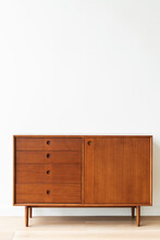 Mid Century Modern Wood Cabinet By A White Wall