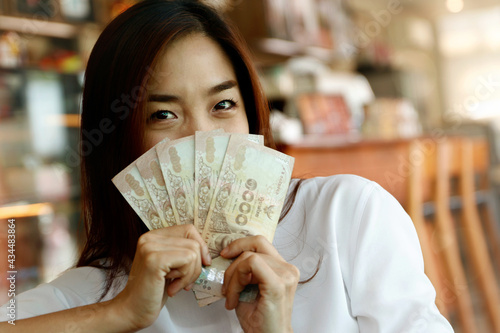 Close up young businesswoman sat joyfully, showing five thousand baht Thai banknotes and arranged in cash in an orderly manner with happy emotions Fototapeta