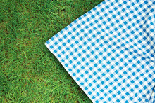 Blue Checkered Picnic Cloth On Green Grass Top View. Checkered Towel Country Design Backdrop. Food Advertisement Display