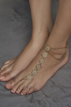 Cropped Shot Of Female Bare Feet On The Gray Cloth. One Of The Feet Is Adorned With Golden Anklet Made As Barefoot Sandal With Multirow Chains And Coins With Engraved Sun Images.