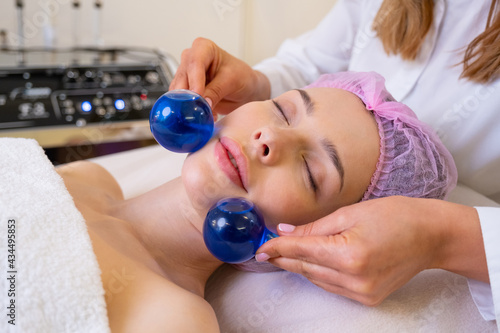 Beautician making a massage of the  face using the blue balls. Woman in a spa salon on cosmetic procedures for facial care. Girl gets massage of a face. Cosmetologist makes face massage.