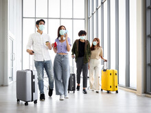 Asian Young Tourist Group With Luggage Wearing Face Mask To Prevent Coronavirus Infection, Standing At The Airport, Waiting Airline Flight At Terminal, Social Distancing And New Normal Travel Concept.