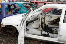 An Old White Wreck Car With Open Door In A Scrap Yard That Were Cleared From Interior
