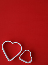 Symbol Of Love Of Man And Woman In The Form Of Two Cutters Hearts On Bright Red Background. Vertical, Copy Space.