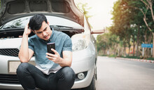 Asian Man Using Mobile Phone Calling For Assistance After A Car Breakdown On Street. Concept Of Vehicle Engine Problem Or Accident And Emergency Help From Professional Mechanic