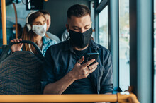 Man Wearing Protective Mask And Using A Smartphone While Riding A Bus