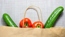Tomatoes And Cucumbers, Which Are Put In A Paper Bag For Shopping.