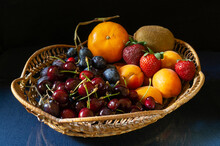 Ripe Fruit In A Basket On The Table With A Reflection