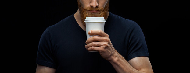 Croped shot of young caucasian bearded stylish man with paper cup of coffee to go over black background. Coffee to go concept.