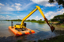 The Yellow Backhoe Is Working At The River Floatin