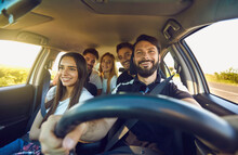 Happy Group Of People Men And Women Smiling In Car, Front View. Safety Driving, Family Travel By Car. Friendship Concept