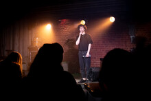 Young Caucasian Male Comedian Performing His Stand-up Monologue On A Stage Of A Small Venue