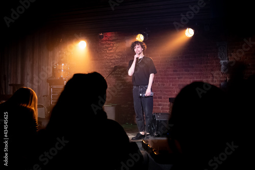 Photo Young Caucasian male comedian performing his stand-up monologue on a stage of a