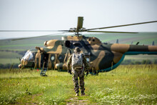 Military Helicopter With Soldiers. Armed Conflict Between Israel And Palestine, Military Action. A Soldier In Camouflage Clothing Goes To A Military Helicopter. Air Armament, Parachutist.
