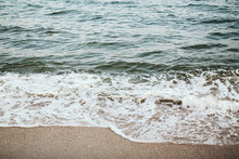 Sea Waves And Foam On Sandy Beach Close Up In Evening Time. Tranquil And Calm Moment. Summer Vacation And Travel Concept. Mindfulness