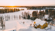Aerial View From Drone Of Frozen Lake Covered By White Snow Near Small Cozy Village With Colorful Houses On North, Bird's Eye View Of Lapland Countryside Land With Scenery Environment .