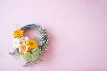 オレンジ、黄色、白のガーベラのブーケリース(ピンクの背景)