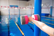 Aqua Aerobics Coach Holding Dumbbells Near The Swimming Pool.