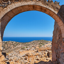 An Roman Arch Of An Ruin Facing A Cliff Of The Mediterranean Sea With Vegetation On It