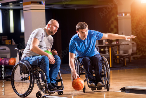 Fényképezés Two young disabled men in wheelchairs playing bowling in the club