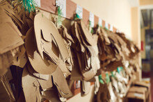 Closeup Shot Of Different Paper Sewing Patterns For Original Brand Leather Boots Hanging On Wooden Peg Rack In Manufacturing Workshop At Shoe Making Factory. Footwear Production Industry Concept