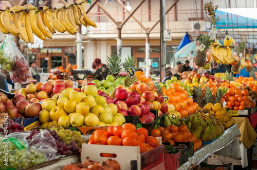 Fotografia Counter of street market stall with various fruits, red and yellow apples, oranges, bananas, pineapples