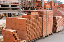 Pallets With Stack Of Redbricks Lying At Warehouse Of Building Materials In Sunny Day