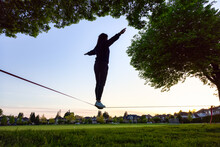 Adventurous White Caucasian Adult Woman Walking On A Slackline Between Trees In A Neighborhood Park. Sunny Sunset. Surrey, Vancouver, British Columbia, Canada.