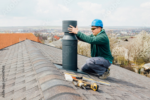 Tela worker with blue helmet on the roof installing iron chimney