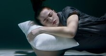 FALLING ASLEEP Young Beautiful Woman In Pyjamas Sinking Deep Under Water With Head On White Pillow Dreaming Slow Motion.