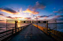 Ocean Beach Fishing Pier In San Diego California During Colorful Sunset With A Sun Star And Bird Flying In The Sky